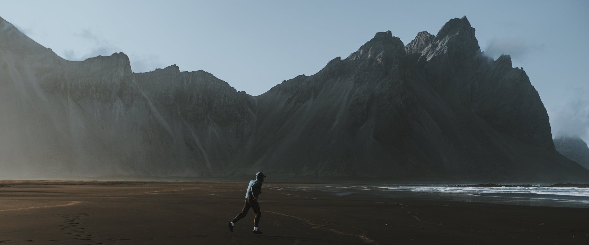 unrecognizable traveler walking on sandy coast near mountains